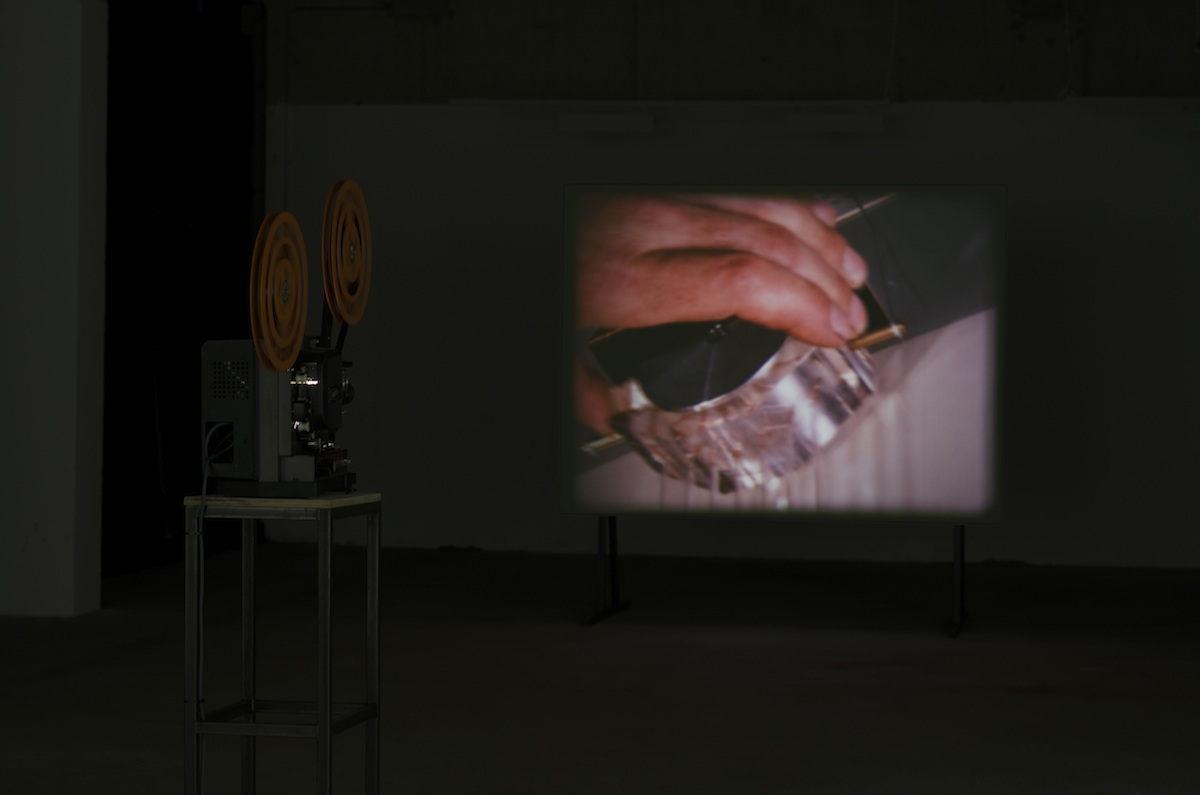 Ronan McCrea, Film Material, 16 mm found film (silent) film projection, looping mechanism, screen, 11'32''. Installation shot of MATERIAL(s) at Green on Red Gallery, courtesy of the artist.
